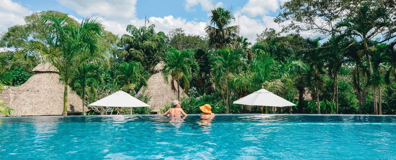 couple lounging at chaa creek infinity swimming pool