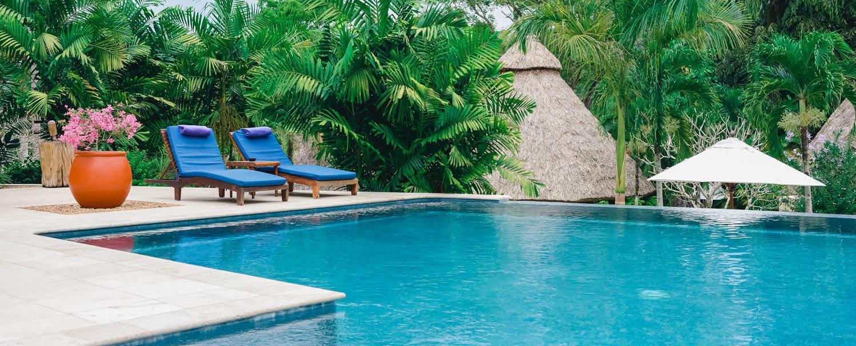 chaa creek infinity swimming pool lounge chairs